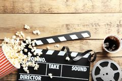 Tasty popcorn, clapboard and movie reel. On wooden background royalty free stock photo