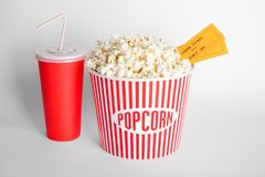 Tasty popcorn, cup with drink and movie tickets. On white background Stock Image