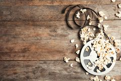 Tasty popcorn and film reel on wooden background, top view stock photography