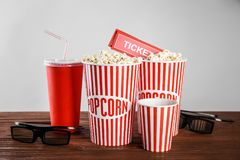 Tasty popcorn, glasses and tickets. On wooden table Royalty Free Stock Photo
