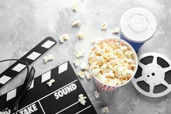 Tasty popcorn, movie reel and clapboard. On grey background Royalty Free Stock Photo
