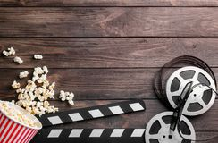 Tasty popcorn, movie reel and clapboard. On wooden background stock image