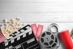 Tasty popcorn, movie reel, tickets and clapboard. On wooden background Royalty Free Stock Photography