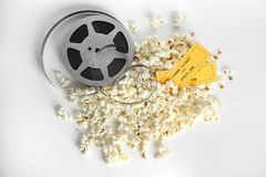 Tasty popcorn, movie reel and tickets. On white background, top view Stock Photos