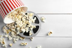 Tasty popcorn and movie reel. On white wooden background royalty free stock photo