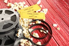 Tasty popcorn, tickets and movie reel. On red wooden background Royalty Free Stock Image