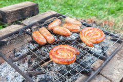 Tasty pork and beef sausages cooking over the hot coals Stock Photography