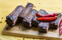 Tasty pork ribs with red pepper on the board Stock Image
