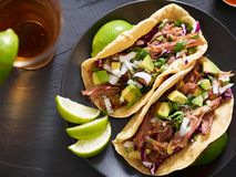 Tasty pork street tacos with onion, cilantro, avocado, and red cabbage. From bird`s eye view royalty free stock photos