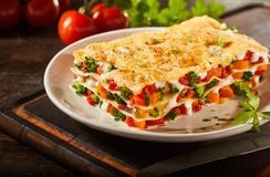 Tasty portion of Italian vegetable lasagna. With melted mozzarella, colorful fresh veggies and pasta serced on a plate as a healthy appetizer royalty free stock images