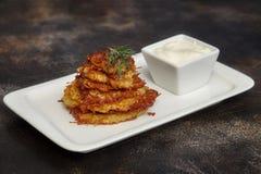 Tasty potato pancakes or latke with sauce. On white plate Stock Photos