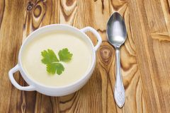 Tasty potato soup with a leaf of parsley, rustic wooden table. Potato and onion vegan, vegetarian healthy cream soup in white cera. Mic bowl and a spoon royalty free stock images