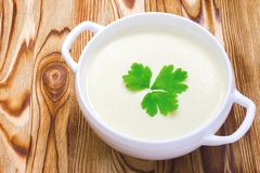 Tasty potato soup with a leaf of parsley, rustic wooden table. Place for text, copyspace. Traditional lunch or dinner. Potato and Royalty Free Stock Photos