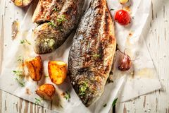 Tasty potatoes and seabream with cherry tomatoes and thyme. On old table royalty free stock photos