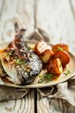 Tasty potatoes and seabream with herbs and tomatoes. On old table royalty free stock images