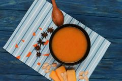Tasty pumpkin soup cream with anise. And slices of pumpkin on a wooden blue background Stock Images