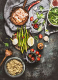 Tasty quinoa salad preparation with wooden spoon , Shrimps , asparagus and various healthy vegetables on rustic kitchen table bac Royalty Free Stock Images