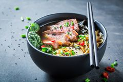 Tasty Ramen soup with chive and algae. On dark table royalty free stock images