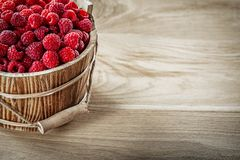 Tasty raspberries in bucket on wooden board copy space.  Stock Photos