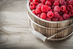 Tasty raspberries in bucket on wooden board.  Stock Image