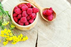 Tasty raspberries in a wooden bowl and a spoon. Top view. The co. Ncept is healthy food, diet, vegetarianism, vitamins Royalty Free Stock Photography