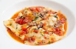Tasty ravioli with tomato sauce and black truffle Stock Image