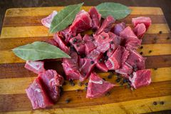Tasty raw  juicy meat. Tasty fresh raw  juicy meat cut into slices with spices black pepper and bay leaf lying on an original wooden background Stock Photo