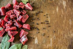 Tasty raw  juicy meat. Tasty fresh raw  juicy meat cut into slices with spices black pepper and bay leaf lying on an original wooden background Stock Images