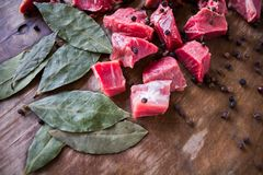 Tasty raw  juicy meat. Tasty fresh raw  juicy meat cut into slices with spices black pepper and bay leaf lying on an original wooden background Royalty Free Stock Images