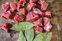 Tasty raw  juicy meat. Tasty fresh raw  juicy meat cut into slices with spices black pepper and bay leaf lying on an original wooden background Royalty Free Stock Photo