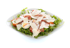 Tasty raw meat salad. Special salad of raw ham, speck, and parmesan cheese on arugula bed Stock Image