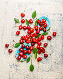 Tasty red cherries with leaves in blue bowls and table, top view composing. Summer fruit  and berries Stock Images
