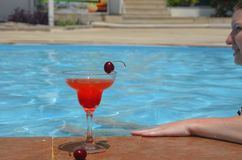 Tasty red cocktail background swimming pool. Margarita cocktail with a glass of cherries royalty free stock image