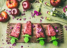 Tasty red homemade fruits ice cream popsicles on wooden kitchen table background with flowers and ingredients Royalty Free Stock Photos