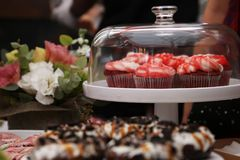Tasty red muffins jn the table. A composition of delicious red muffins, freshly baked donuts and colourful flowers royalty free stock photo