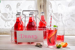 Tasty red orangeade in bottle with citrus fruit Royalty Free Stock Images