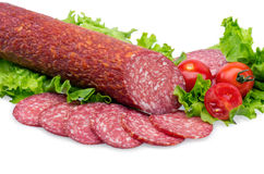 Tasty red salami. Tasty red sliced salami decorated with vegetables stock photos