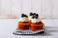Tasty red velvet cupcakes on wooden table. royalty free stock photos