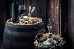 Tasty red wine with camembert cheese and demijohn. Tasty red wine with camembert cheese on old wooden barrel and demijohn Royalty Free Stock Photo