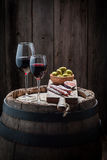 Tasty red wine in glass with olives and cold meats on wooden barrel Stock Images