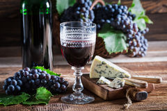 Tasty red wine with grapes and cheese. On old wooden table Stock Images