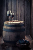 Tasty red wine with grapes and old barrel Royalty Free Stock Photos