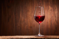 Tasty red wine poured in the elegant glass standing on the wooden stand against wooden wall background. Brightly wine and fragile goblet. Natural material and Royalty Free Stock Image