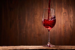 Tasty red wine poured in the elegant glass standing on the wooden stand against wooden wall background. Brightly wine and fragile goblet. Natural material and Royalty Free Stock Images