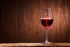 Tasty red wine poured in the elegant glass standing on the wooden stand against wooden wall background. Brightly wine and fragile goblet. Natural material and Stock Photography