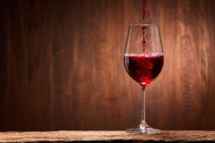 Tasty red wine poured in the elegant glass standing on the wooden stand against wooden wall background. Brightly wine and fragile goblet. Natural material and Royalty Free Stock Photography