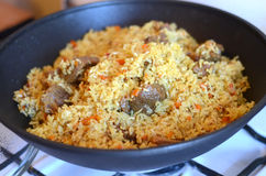 Tasty rice in a pot. Delicious pilaf with meat and rice just cooked in a black cauldron on a gas stove Royalty Free Stock Photo