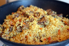 Tasty rice in a pot. Delicious pilaf with meat and rice just cooked in a black cauldron on a gas stove Stock Image