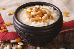 Tasty rice pudding with nuts and raisins in a bowl close-up. hor Royalty Free Stock Photo