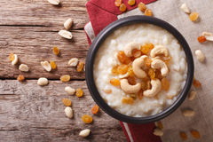 Tasty rice pudding with nuts and raisins close-up. horizontal to Stock Photos